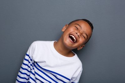 Boy in a white jumper laughing